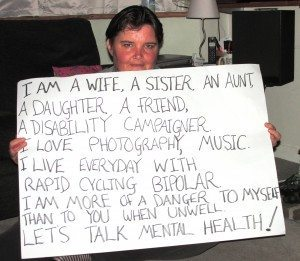 "Paula Peters holding a banner - ""I am a wife, a sister, an aunt, a daughter, a friend, a disability campaigner. I love photography, music, I live everyday with rapid cycling bipolar. I am more of a danger to myself than to you when unwell. Lets Talk Mental Health"""