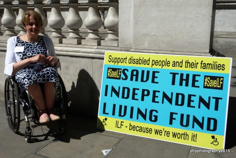Dame Tami Grey Thompson next to the giant Save the ILF Postcard that was produced for the Westminster Abbey Grounds Occupation, and has been on every ILF protest since