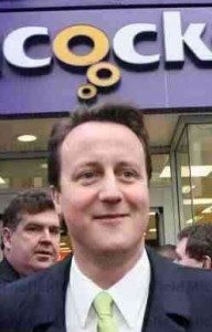 """Cameron standing underneath a portion of a sign saying """"Cock"""""""