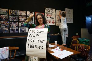 "Woman standing in front of an exhibition. She is holding a poster which says ""Cut your crap not our lifelines"""