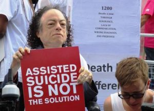 Lizz Carr with placard which says ASSISTED SUICIDE IS NOT THE SOLUTION