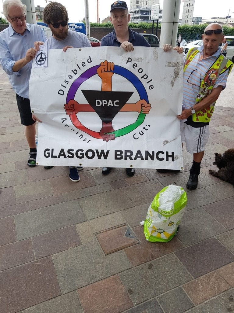 DPAC Glasgow members holding a DPAC Glasgow Branch banner at the protest